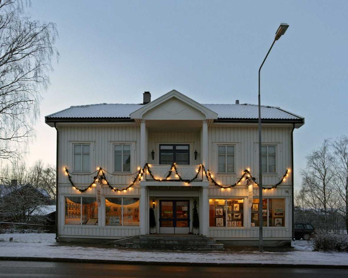 Julebelysning.  Hvit julebelysning i grangirlander på eldre forrretningsbygning.