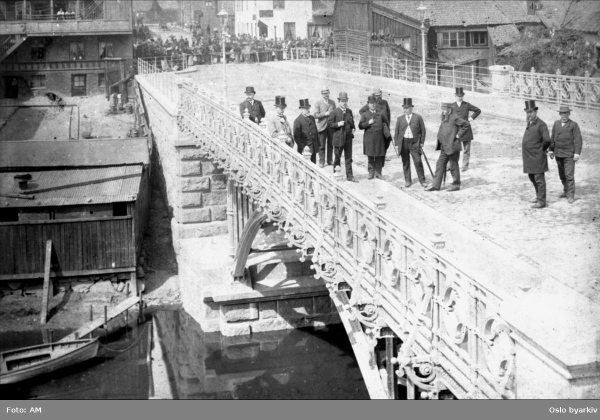 Hatteprydete menn på Hausmanns bro, ved åpningen 30. juni 1892. Folkemengde som venter bak sperringene. Stadsingeniøren - Fotografier af Kristiania (albumtittel). Akerselva.