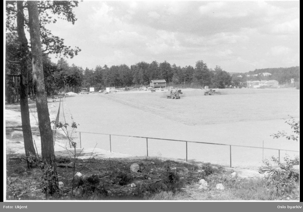 Idrettsparken sett mot nord mot bebyggelse i Vetlandsveien. Såing / bearbeidelse av fotballfeltet fra traktorer. Trasopbanen