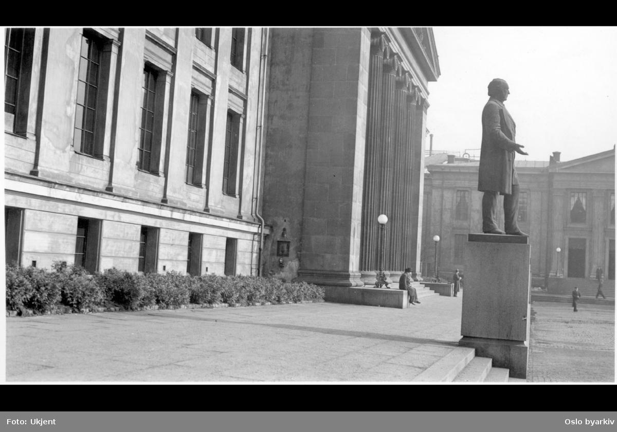 """Blomsterbedene foran Domus Media (Midtbygningen) Karl Johans gate 47. Minnesmerket (statue) over Anton Martin Schweigaard. Domus Academica (Urbygningen) i bakgrunnen. Albumtittel: """"Universitetshaven & plassen. Uranienborg"""""""