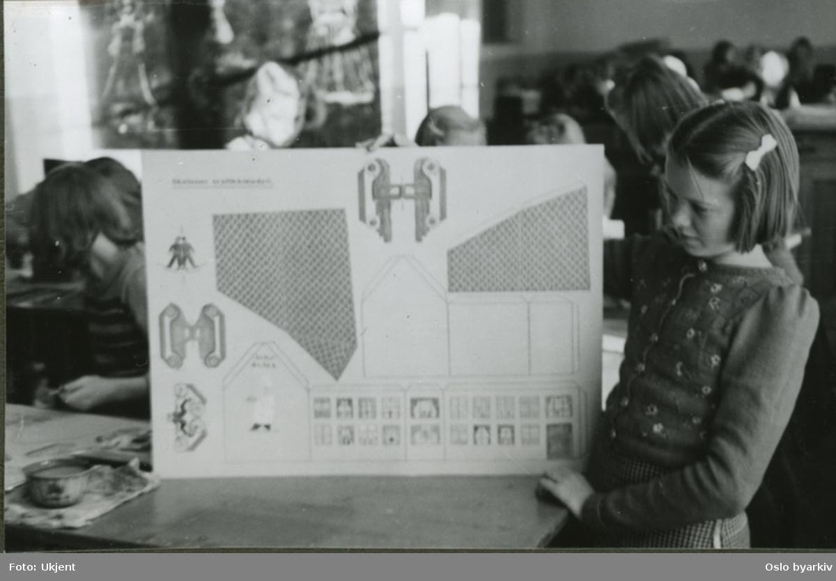 """Jenter som viser fram en plansje i formingstimen. Albumtittel: """"Sofienberg skole femti år - første september 1933."""""""
