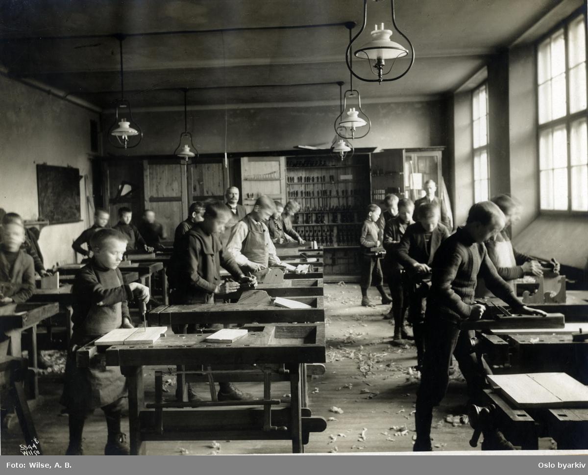 Majorstua (folke)skoles sløydsal. Elever arbeider under sløydlærers strenge blikk. Høvelbenker. Verktøyskap. Taklamper. (Jfr. bilde A-10001/U/011/046.) Bilde brukt i kommuneberetningen fra 1887 - 1911.