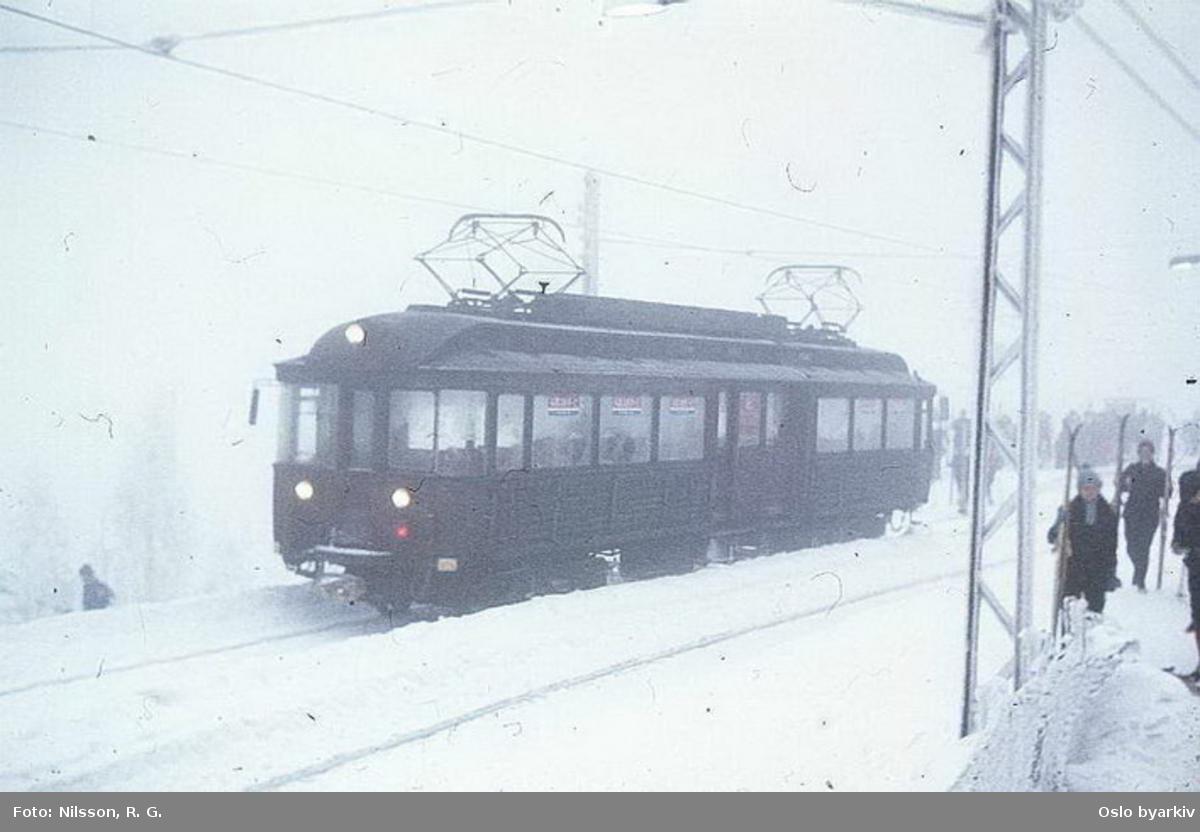 Holmenkollbanens vogn 112 ut fra ankomstplattform, snø og tåke på Frognerseteren stasjon.