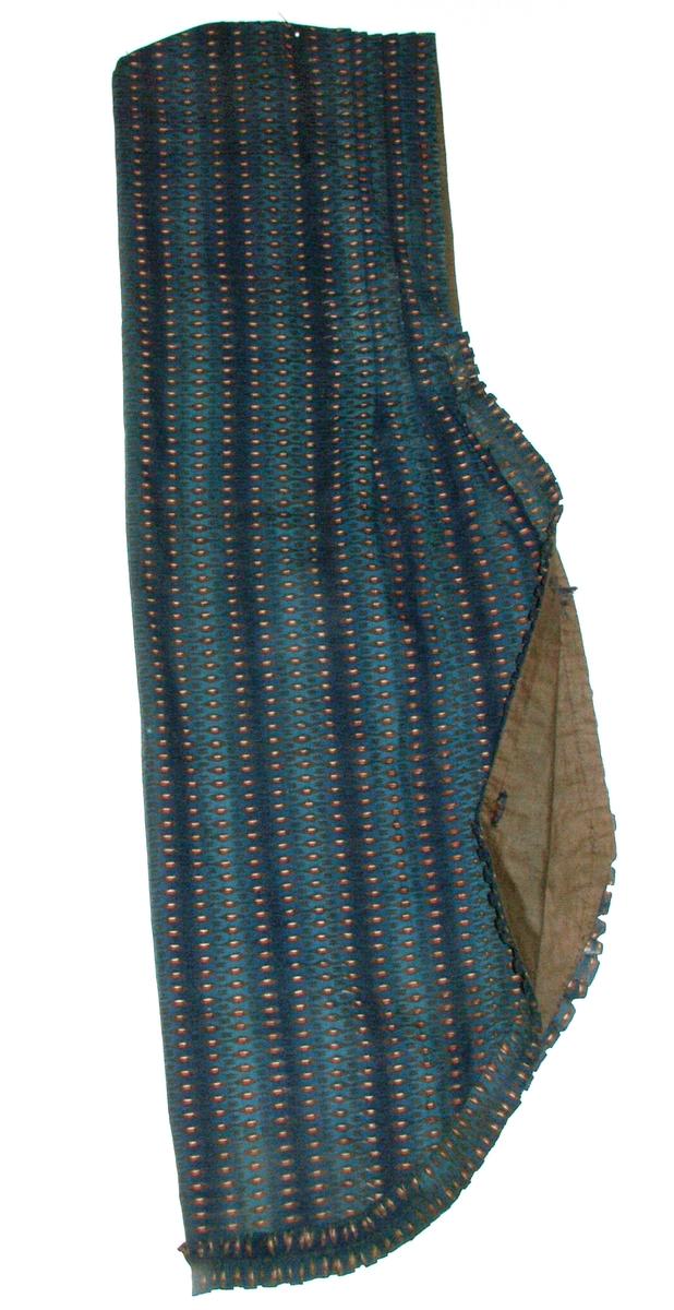 Plagget har en rysjekant i hovedstoffet. Det har opprinnelig vært seks knytebånd i silke, tre på hver side.