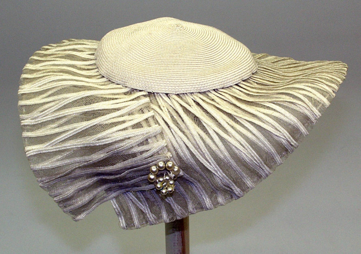 Flat pull med stor bunn avsluttes med perle dekor. Ståltråd i ytterkant. Smale bånd sydd til ett transparent nylon stoff. Dobbel effekt. Svettebånd og hattestrikk.