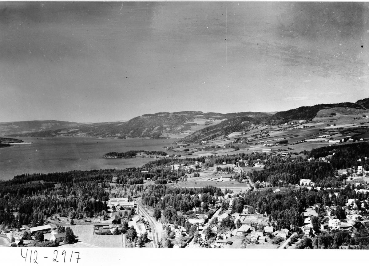 Flyfoto av Moelv sentrum med Ringsbygda og Brøttum i bakgrunn.