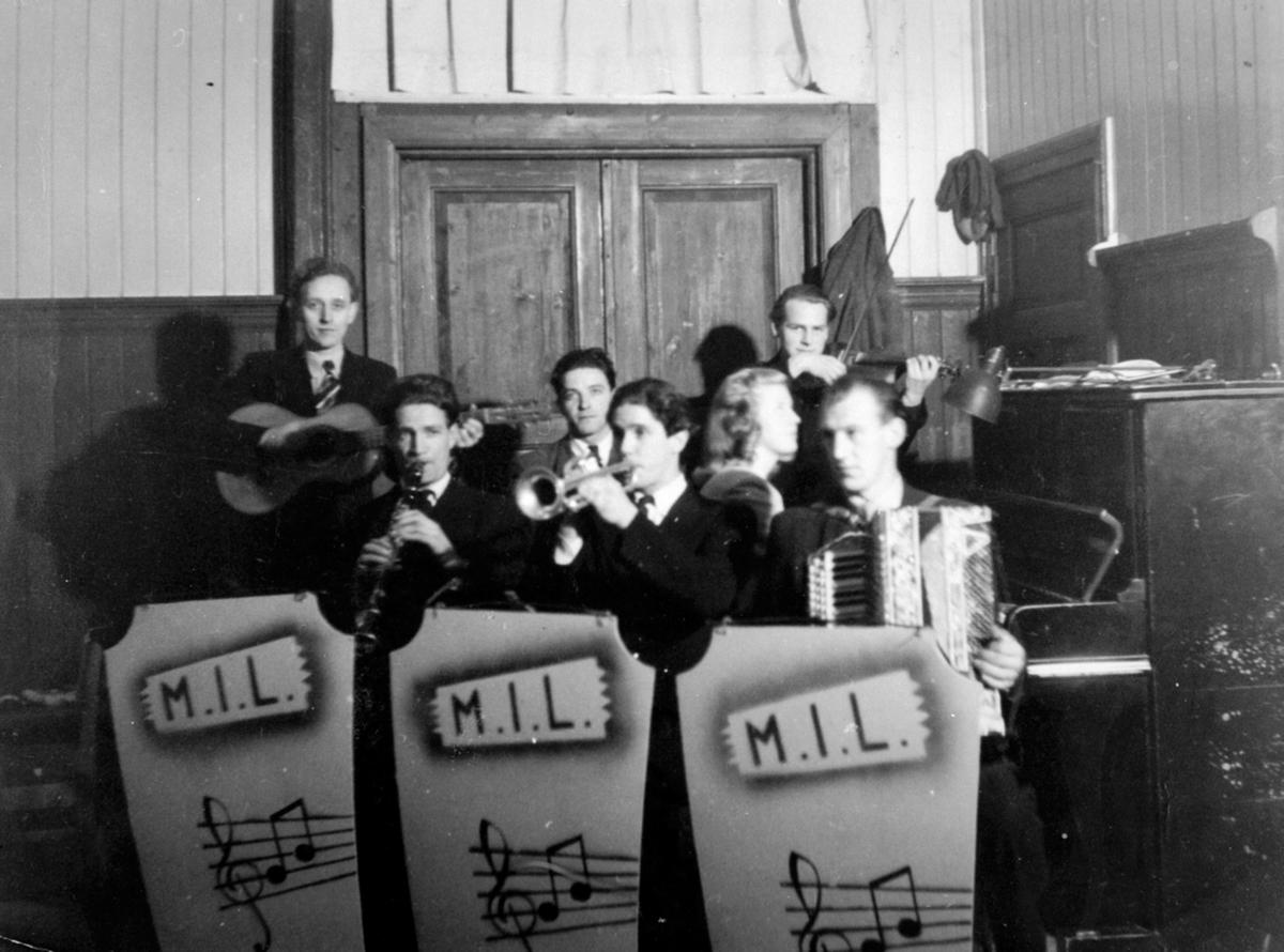 Gruppe musikere i Folkets Hus, Moelv. Moelven Idrettslags orkester. Fra venstre er Olaf Hovde, Magnus Kamperud, Leif Bakken. Første rekke er Reidar Olsen, Thoralf Andersen, Sigurd Magnussen, ved piano Inger Tangen.