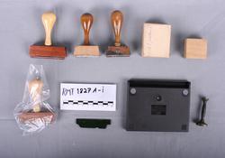 Åtte stempel og en stempelpute. Et av stemplene ligger inni en gjenomsiktig plastpose. Det er fire forskjellige typer stempel.