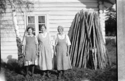 Tre kvinner ved en husvegg og en stabel med staur.