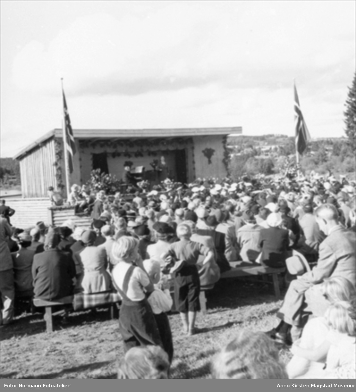 Kirsten Flagstad synger ved en friluftskonsert på Domkirkeodden, Hamar 30. august 1953. Ved klaveret Amund Raknerud. Kirsten Flagstad at an open air recital at Domkirkeodden, Hamar 30. August 1953. Amund Raknerud at the piano.