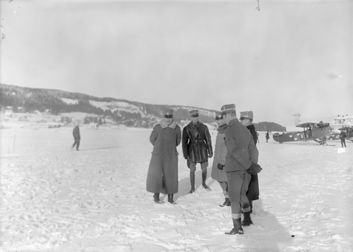 Inspektion på flygstationen i Östersund, vintertid, 1926. Fem män står i en klunga. Flygplan Phönix E1 märkt 4196 i bakgrunden.
