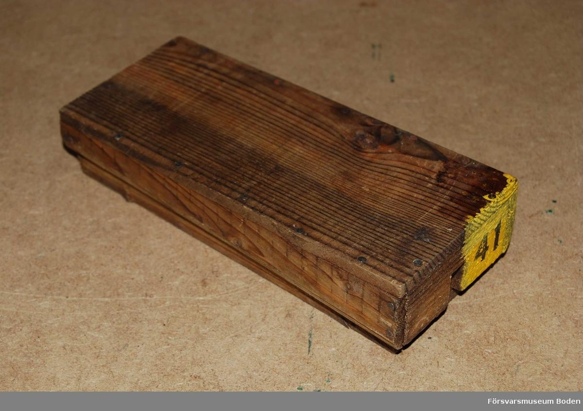 Trälåda med ledat lock till trampmina, saknar innehållet förutom träkloss. På den gavel som ej är ledad finns ett hål där slagtändaren apteras.