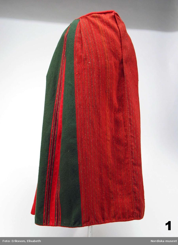 Kjol av halvylle, varp av vitt lingarn med varptäckande inslag i tuskaft med entrådigt ullgarn, sydd av ett stycke med söm mitt fram. Breda randbårder i 2 nyanser  rött, mörkblått, grönt samt flamfärgat garn i grönt/vitt resp. rött/vitt på omväxlande röd eller grön botten. Mitt fram där det inte syns under förklädet är  bottenfärgen rödbrun med smala ränder i rött och grönt, för att spara på de dyrare färgämnena. Kjolen slät framtill och med lagda veck bak, bredare vid sidorna och smalare där de möts mitt bak. Vecken lagda så att färgerna får en dekorativ effekt.  Midjelinning av röd vadmal, sprund mitt fram i sömmen med spår efter hake och hyska i midjan. Kjolkanten skodd med ett centimeterbrett grovt  ylleband i rött, grönt och brunrött där den röda randen bildar en synlig kantsnodd åt rätsidan. Inuti kjolen ett fasttråcklat rött band för utställningsändamål. Ett annat rött band , inte inmärkt, fastnäst med ett stygn inuti kjolen, även detta band är utställningsrekvisita. Hör ihop med en hel kvinnodräkt från St. Tuna som var bland det första Artur Hazelius köpte in till sina samlingar. Kjolen har fått inventarienummer 1. Jfr denna kjol   med inv.nr 111.658 som är av samma typ och enligt uppgift från 1840-talet.   I gott skick. /Berit Eldvik 2011-10-04