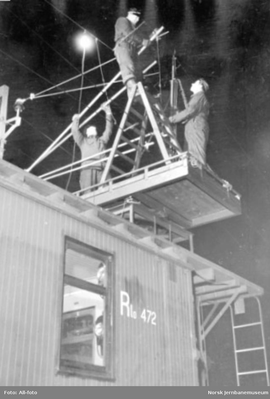 Arbeid med kontaktledning fra taket på en revisjonsvogn