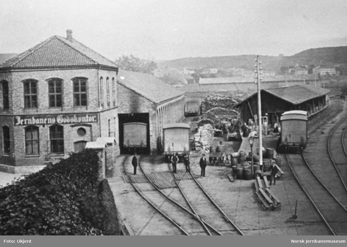 Jernbanens godsekspedisjon i Oslo med godsvogner, diverse last og jernbanefolk