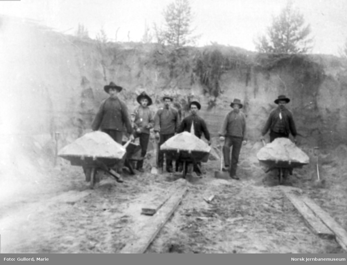 Anleggsarbeidere med trillebårer i en skjæring på vestsiden av brua over Glomma ved Haugsfoss