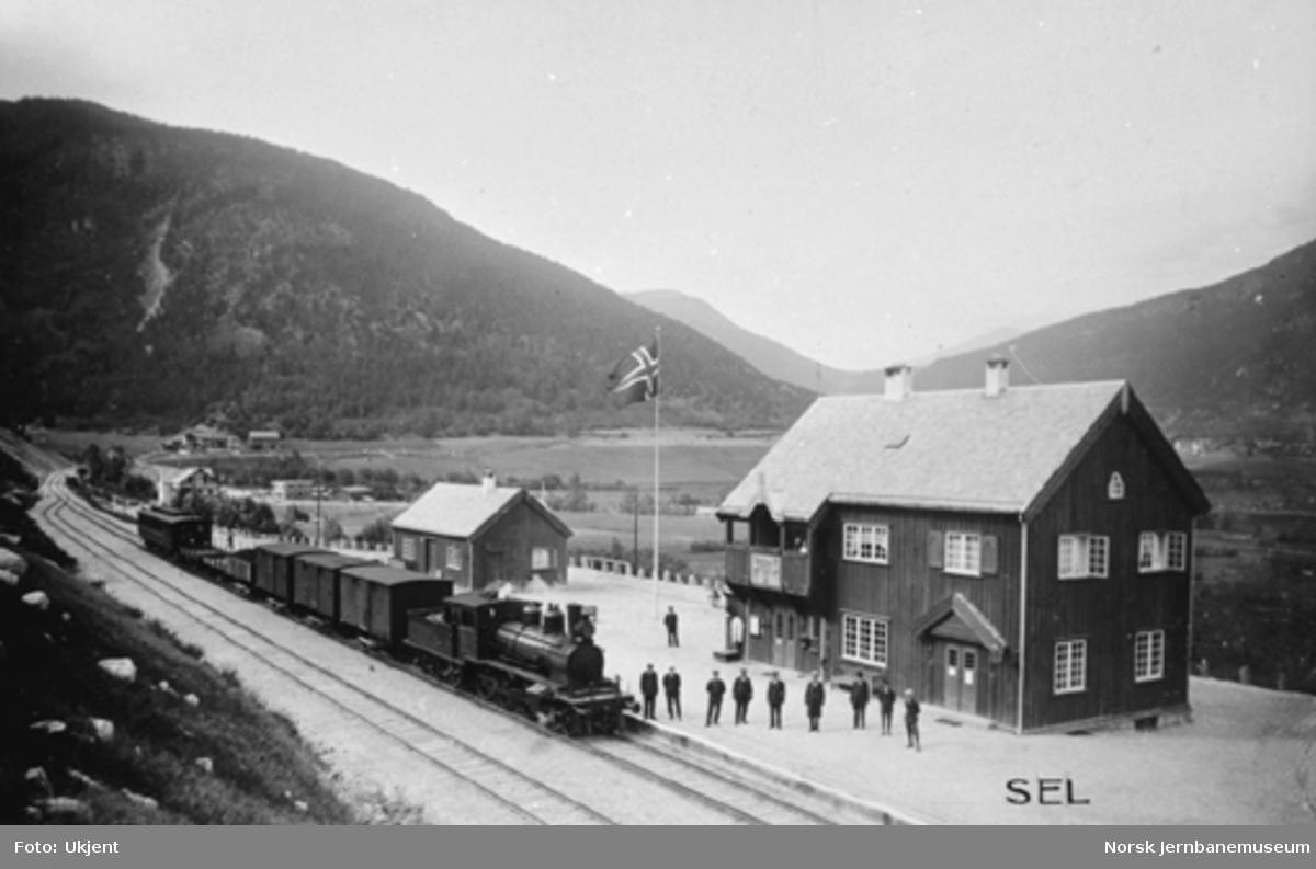 Sel stasjon med personalet oppstilt på plattformen og et damplokomotiv av type 21 med blandet tog i spor 1