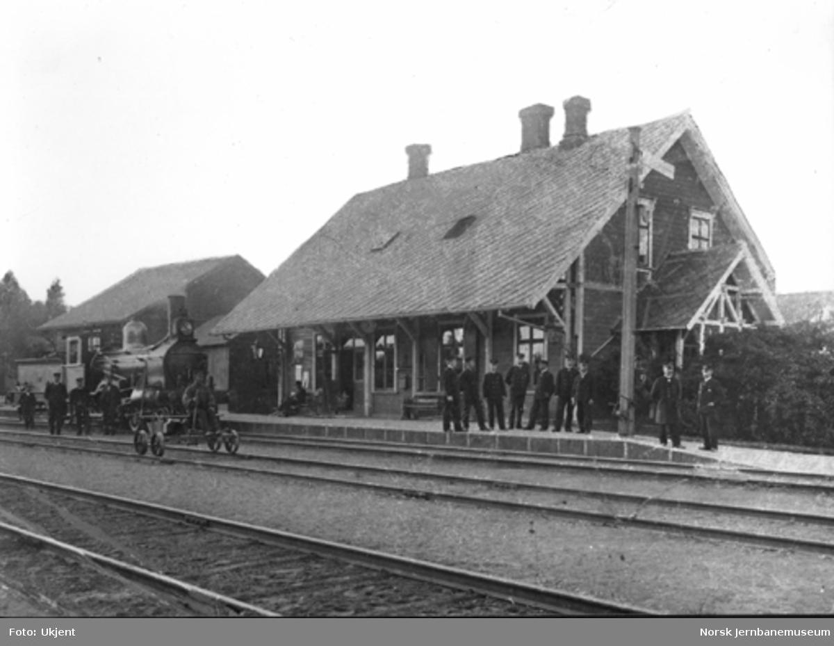 Kornsjø stasjon med stasjonsbygning og godshus : damplokomotiv i spor 1, håndtralle i spor 2