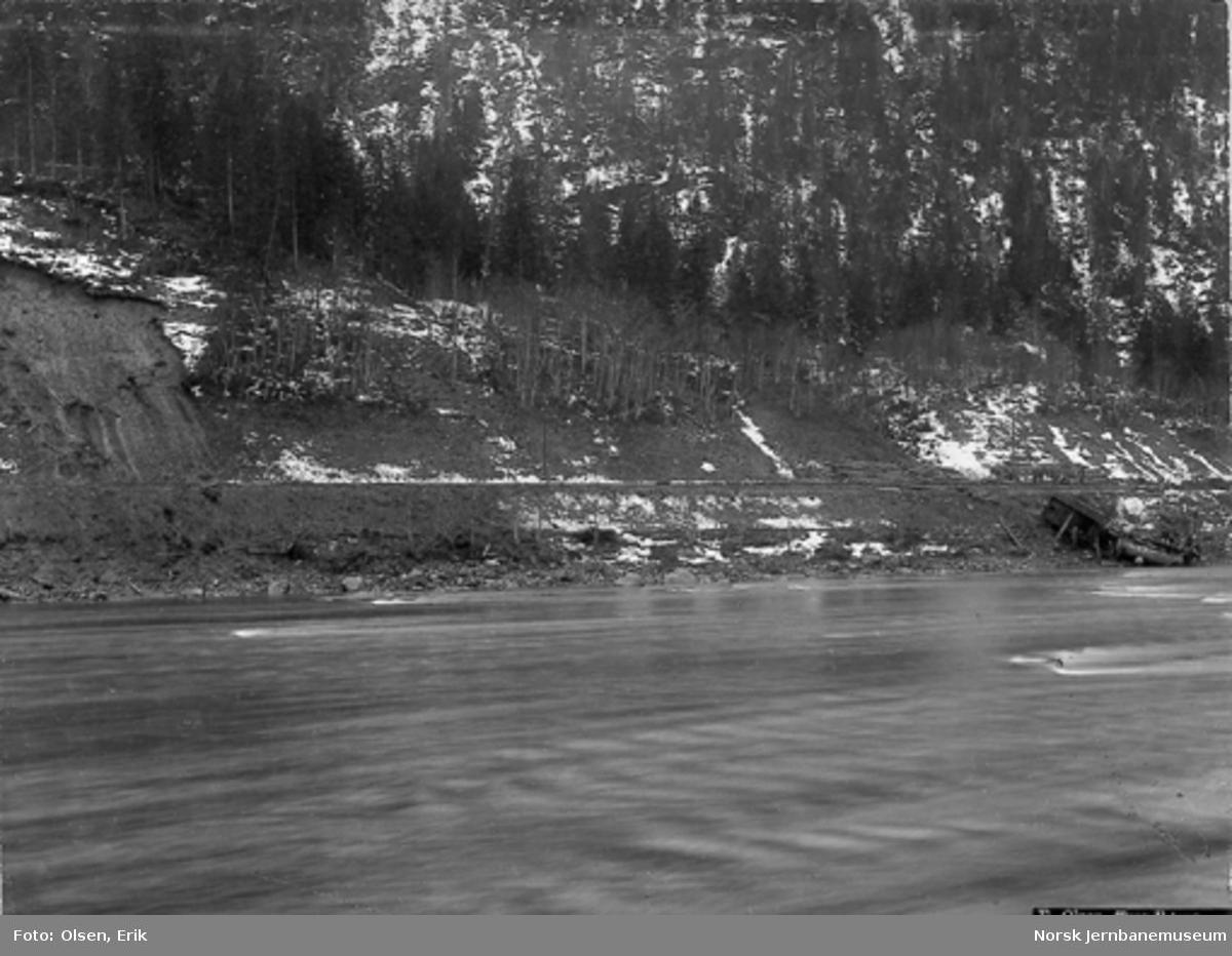 Avsporet damplokomotiv type 9a nr. 57 ved kilometer 54,8 mellom Flornes og Hegra : sett fra motsatt elvebredd og med et ras til venstre i bildet, 70 meter fra det avsporede lokomotivet