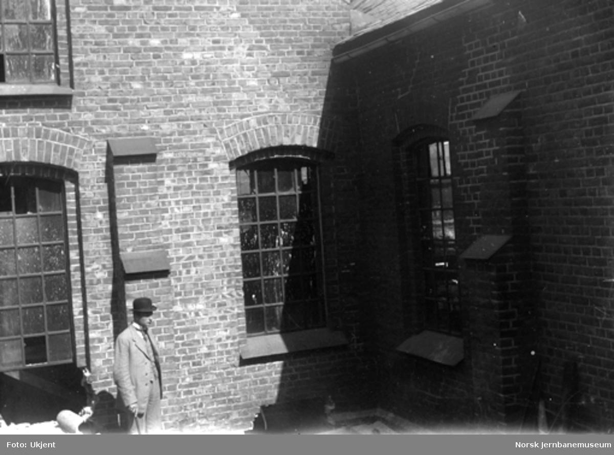 En mann utenfor en lokomotivstall eller en verkstedbygning