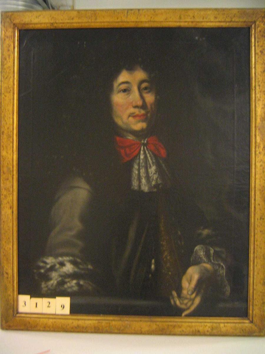 Mann m/ mørk frakk med pelskant på ermene, rød sløyfe og hvite kniplinger i halsen, stor svart parykk.