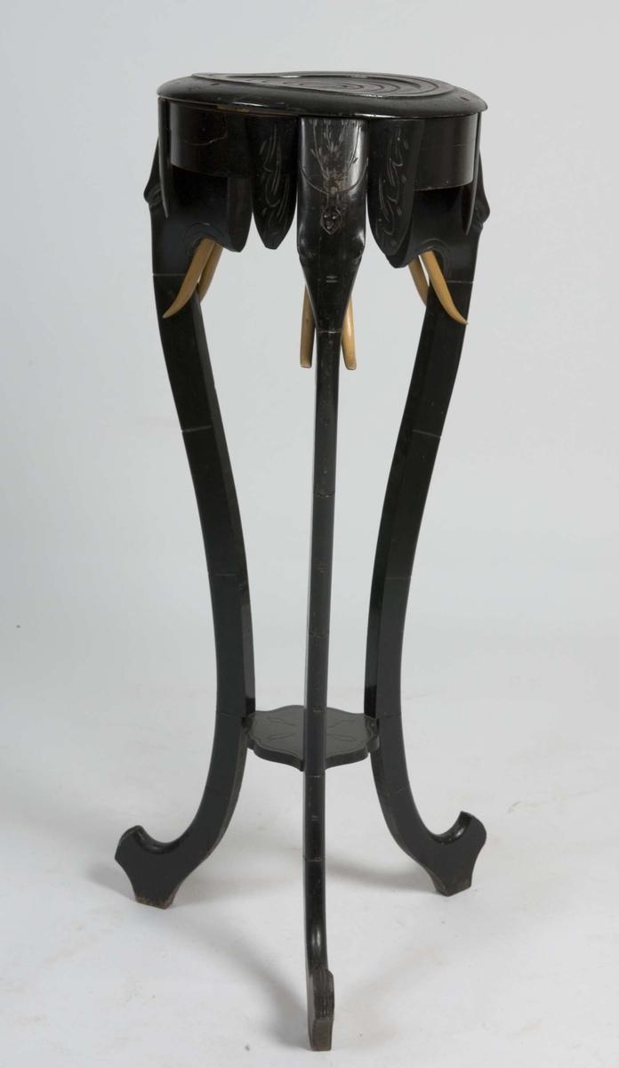 3 stk S-formete ben som hode av elefanter med lyse tenner og snablene ned mot gulvet. Topplaten er rund med dreid konsentriske spor. Piedestallbordet er malt svart foruten tenner som er ubehandlet lys tre. Liten hylle 25 cm fra gulv.