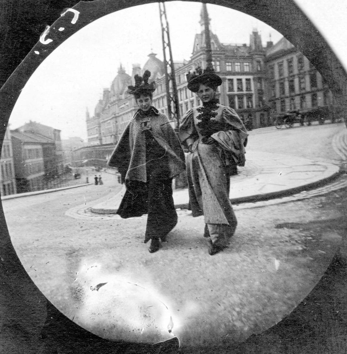 Frøknene Ingeborg Willumsen og Lilli Heiberg spaserer med ryggen til Victoria Terasse, Oslo.