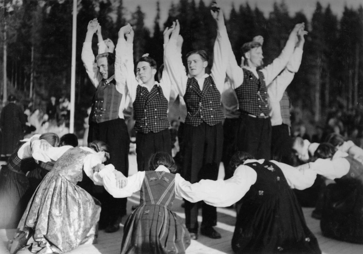 Folkedansoppvisning, antagelig på Maihaugen (De Sandvigske Samlinger). Bunadskledde menn og kvinner danser en form for runddans.
