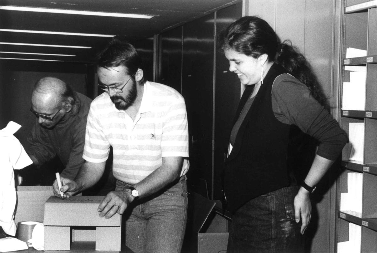 Wilse-negativ pakkes av personale fra Nasjonalbiblioteket, Mo i Rana, 15.8.1990. Fra venstre: Arnfinn Småli, Thomas Røjmyhr og Kari Mina Kvammen.   Thomas Røjmyhr og Arnfinn Småli (han med minst hår) pakker N-serien for transport.