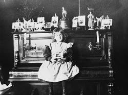 Karen Q. Wiborg sitter på piano i stue, Meltzers gate 9, Osl