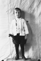 Portrett av gutt stående på krakk foran opphengt bakteppe, u
