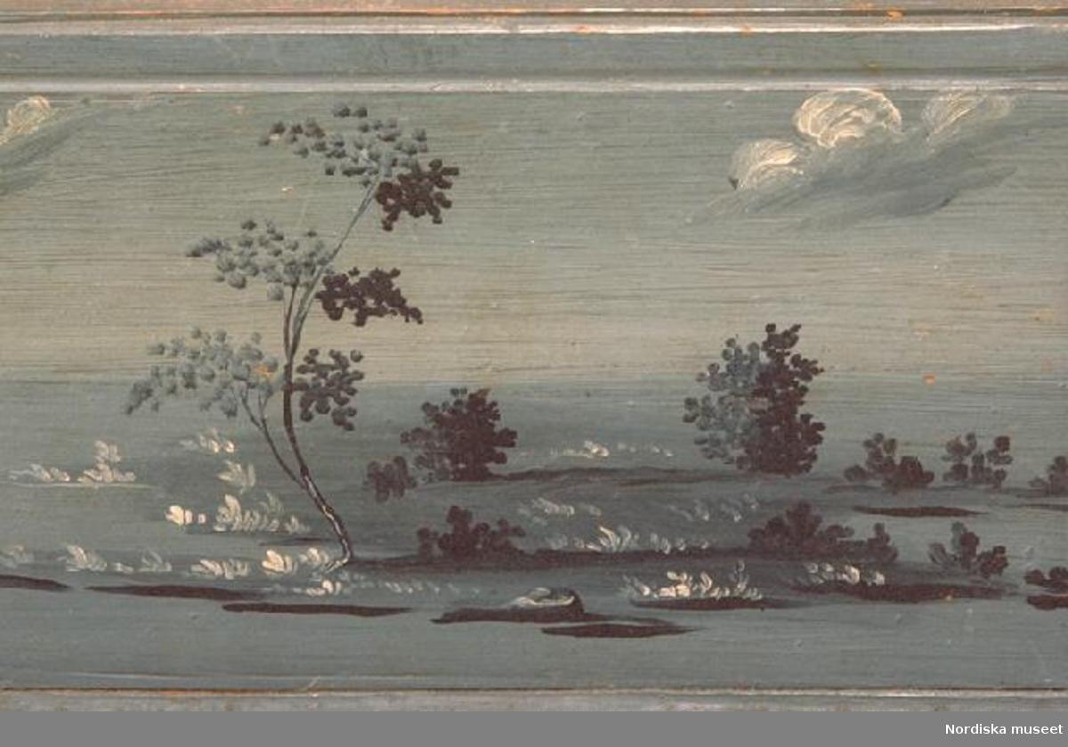 """Huvudliggaren: """"a-c Ask, trä, blåmålad, landskapsbilder på sidor och lock; delad i 3 fack; lönnfack under botten; skjutlock; från Ljusdal sn, Hälsingland. I[nköpt] 22/9 1936 från konstnären Bror Hillgren, Stockholm jämte 206.818 - 206.820 [...].""""  Inventering Sesam 1997-1998: L 26, B 19, H 12,5 cm Ask (a), rektangulär, med skjutlock (c), av barrträ. Utanpåliggande botten, fästad underifrån med spikar samt en trädymling, med fotlist. Sidorna sammanfogade genom sinkning. Ena gaveln (b) löstagbar och bakom den finns ett lönnfack nedtill vid botten, utskuret snitt på gavelns utsida. Skurna lister i massivträet upptill på kanterna. Svagt fasade kanter på locket, skuren list spikad vid ena kortsidan att ta i vid öppning. Invändigt uppdelad i tre fack, skurna spår i väggarna tyder på att det funnits en mellanvägg till, alltså fyra fack från början. Utvändigt målad i blått i olika nyanser, litet vitt, mycket dekorativa och välgjorda landskapsmotiv på samtliga sidor och locket. Agnetha Blomberg 1997"""