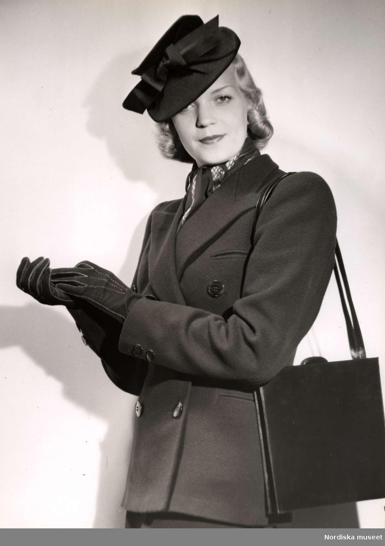 Dammode visas på Nordiska Kompaniet 1939. En kvinnlig modell poserar iförd dubbelknäppt jacka, liten hatt med rosett och handskar. Över axeln hänger en väska.