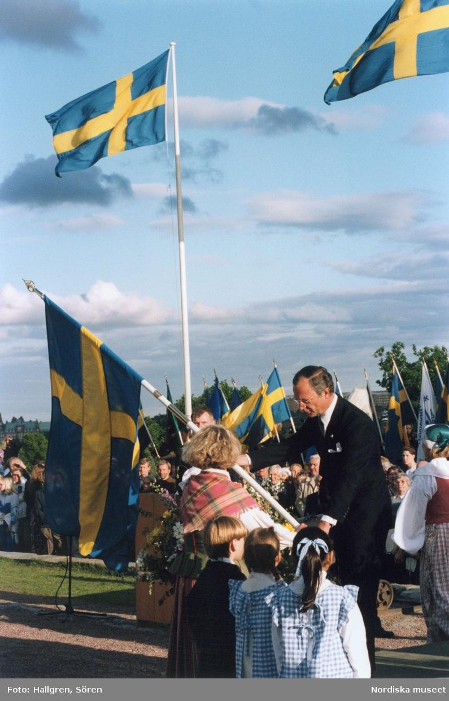 Sveriges Nationaldagsfirande på Skansen, Svenska Flaggans dag. Kung Carl XIV Gustav delar ut en fana till kvinna folkdräkt.