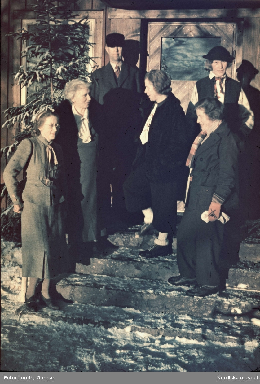 Dalarna. På Långbergsgården i Tällberg på vintern med gruppbild av fem kvinnor och en man i vinterkläder på förstutrappa.