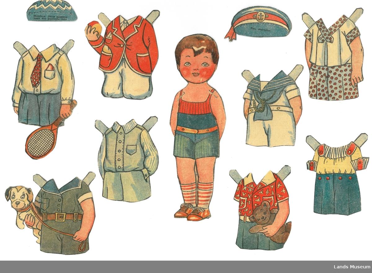 Papirdukke med klær frå utklippsark, to av tilbehøret er også teikna av og laget kopier av.  A- dukke, gutt, 19 x 5,5 cm B- dress med kortbukse, 6 x 9 cm C eks.1- Matrosdress, 7,5 x 6 cm C eks.2- Matrosdress, 7,5 x 6 cm D eks.1- lue til matrosdress, 3 x 6 cm D eks.2- lue til matrosdress, 3 x 6 cm E- leikedrakt med bamse, 8 x 5 cm F- leikedrakt med hund, 8 x 9,5 cm H- dress, lys blå, 8,5 x 6 cm I- sett, blå bukse og gul bluse, 7 x 7 cm J- sett, rød jakke og kvit bukse, 8,5 x 8 cm K- skoleuniform med rødt slips, 11,5 x 6,5 cm L- lue til skoleuniform, 2,5 x 5 cm