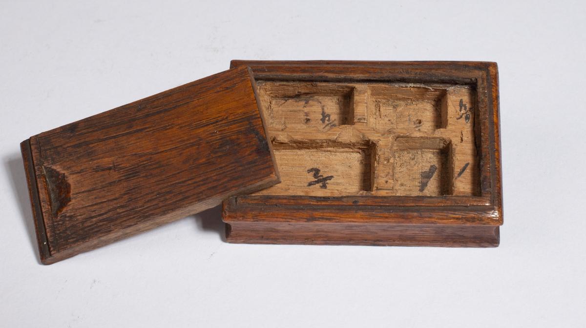 Lite, rektangulært etui med hull inni, laget til oppbevaring av lodd.