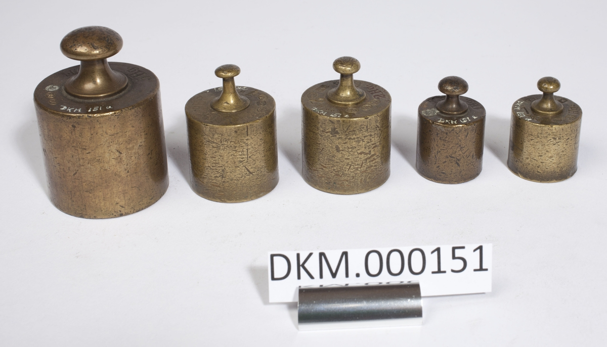 Fem sylinderformede lodd i ulik størrelse. Kontrollstempel i hvert lodd.