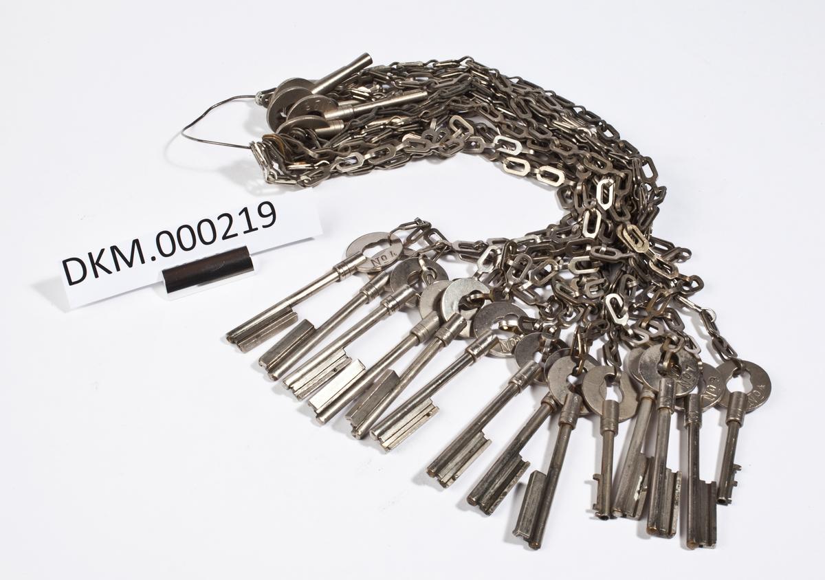 Knippe med 18 nøkler i stålkjettinger.