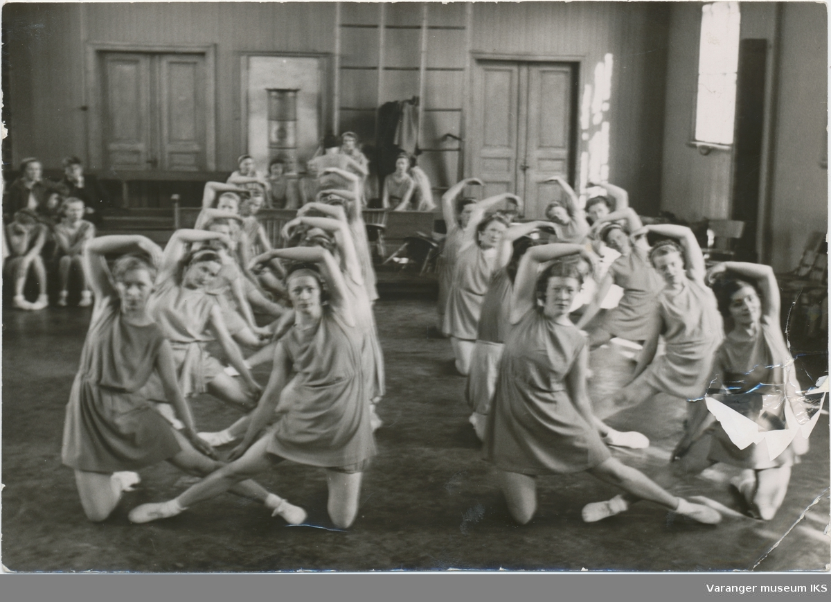 Unge kvinner øver i den gamle gymnastikksalen