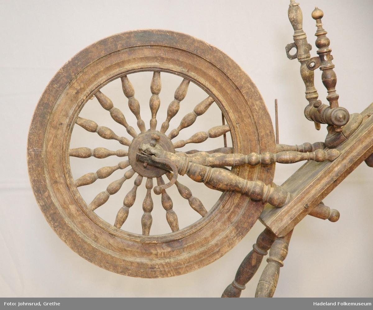 Rokk med skrått bryst, tre bein og hjul med 16 eiker. To ulike jomfruer. Mangler blant annet fotplate, tein og rokkhode. Dreid og skåret dekor.