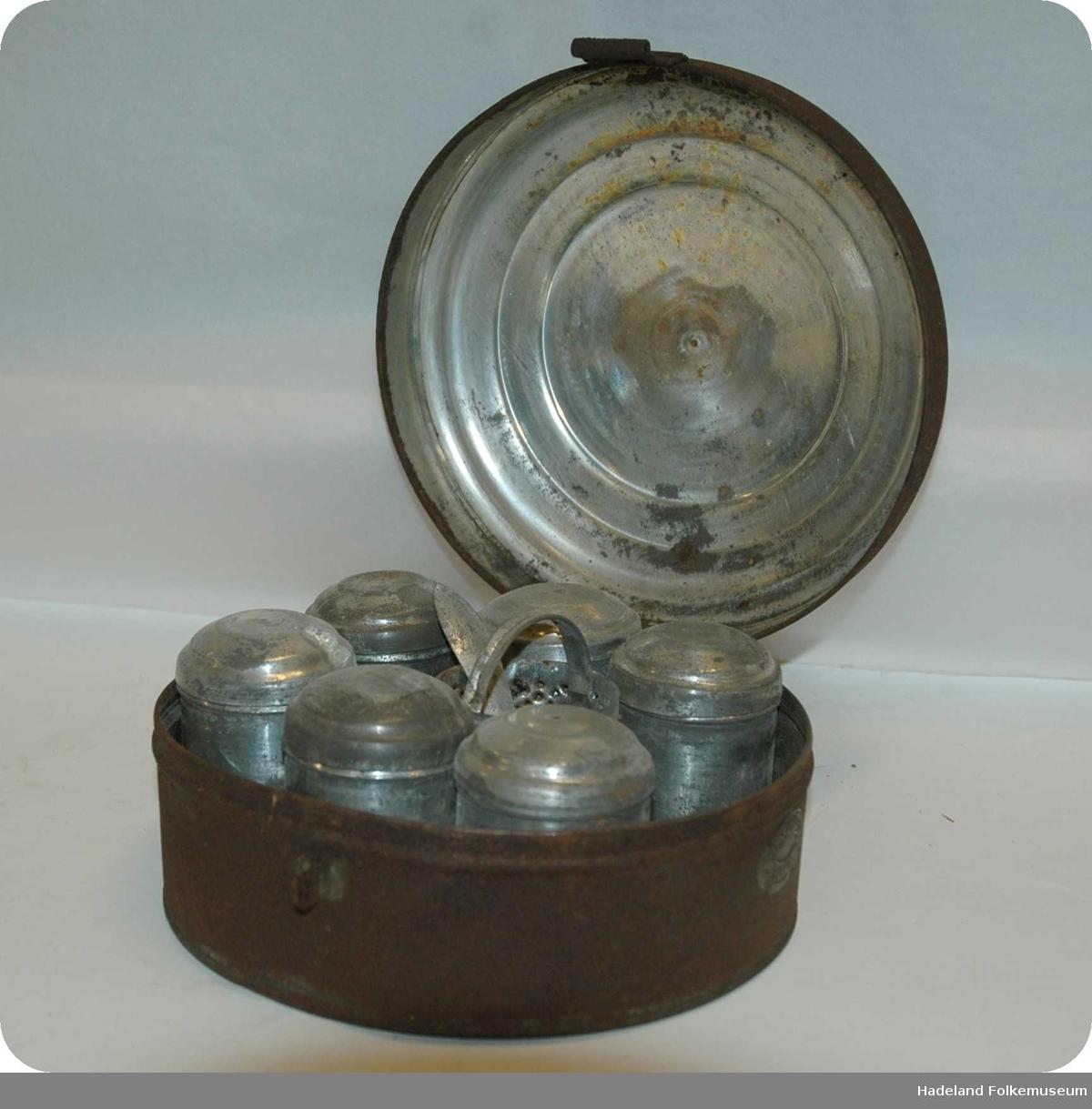 Skrin i blikk og jern med beholdere til krydder. Rundt skrin med hengslet lokk. I skrinet: 6 sylindriske bokser med lokk (b-m) 1 lokk (til en manglende boks) (n) 1 syløindrisk rivjern (o) 1 skje(p). Rust, særlig på skrinet.En boks mangler.