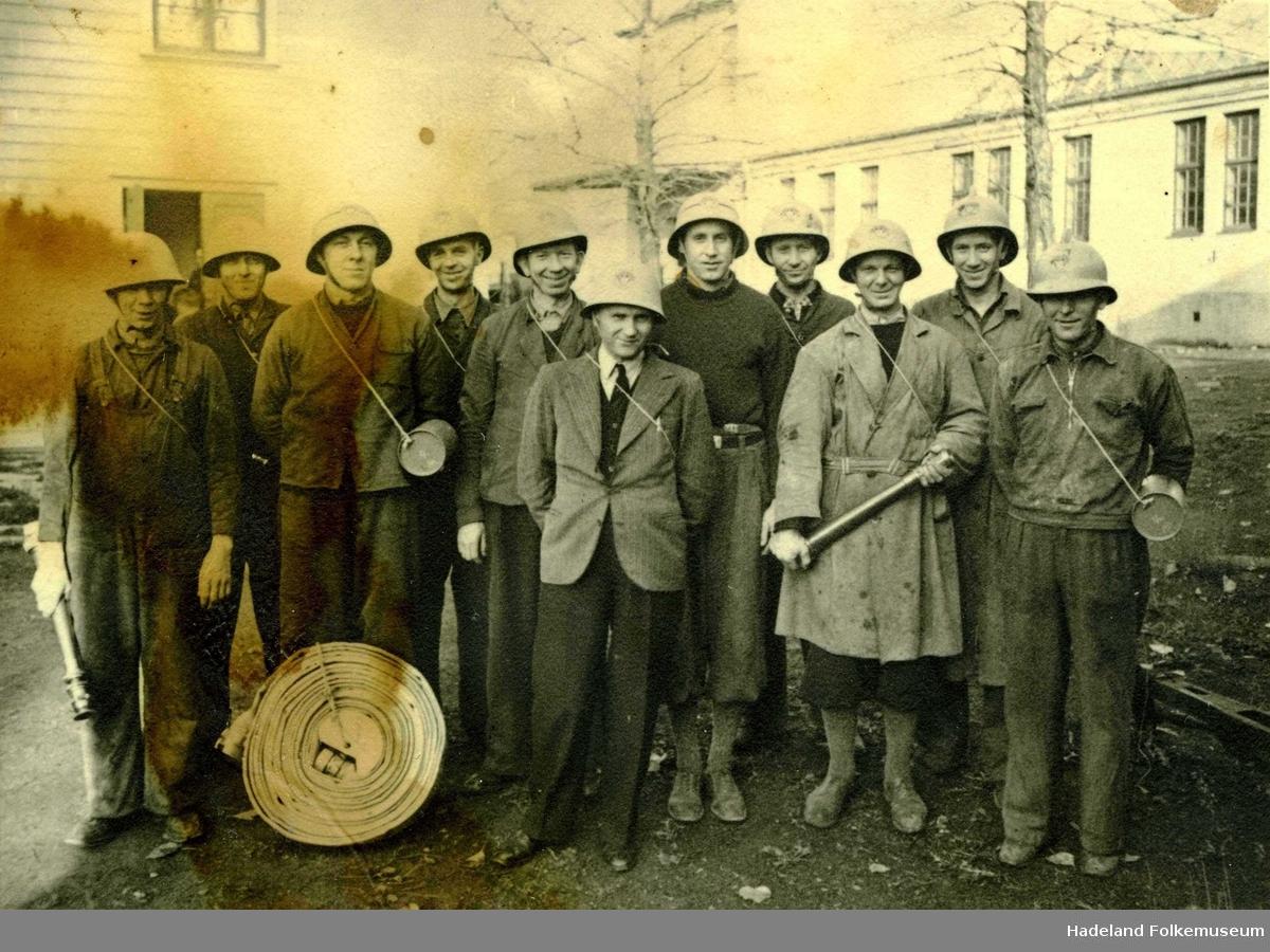 Bedriftsbrannvern ved Andfossen Bruk, gruppe med 11 menn med hjelmer og brannslange.