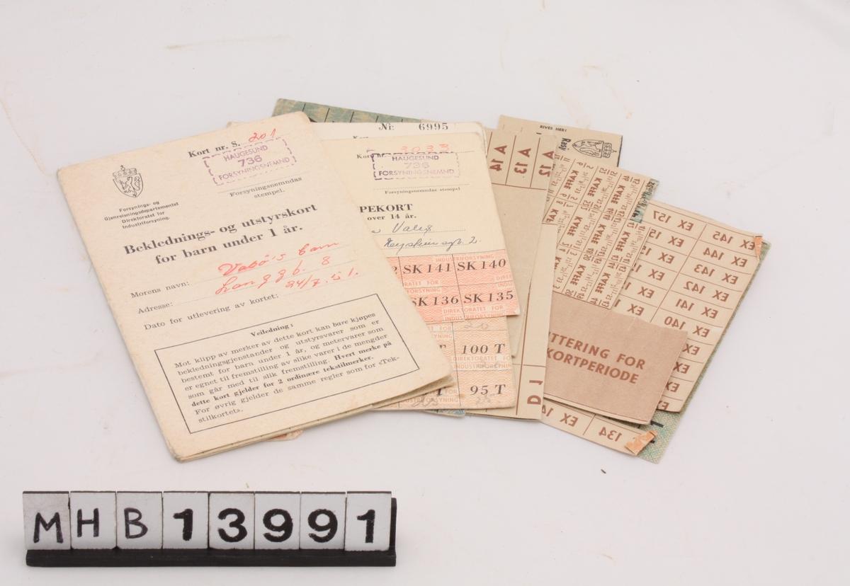 Konvolutt med rasjoneringkort fra andre verdenskrig:  - Tekstilkort - Strømpekort for kvinner over 14 år - Beklednings- og utstyrskort for barn under 1 år - 2 Ekstrakort for 46. kortperiode - Ekstrakort for 45. kortperiode - 2 Rasjoneringskort for matvarer