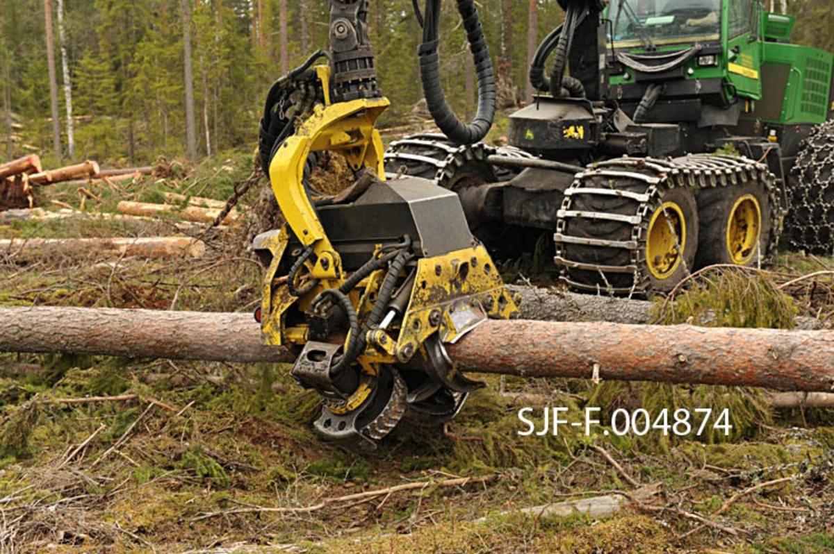 Bilde av skogsmaskinen John Deere 1270 som rydder opp et vindfallsområde etter stormen Dagmar. Bildet viser hvordan skogsmaskinen arbeider med opprydningen, noe som er utfordrende da maskinen er konstruert for å hugge stående skog. Bildet er tatt på en hogstflate i Sormerudskogen i Elverum, hvor det var et stort felt med stormfelte trær øst for Rv. 2, i forbindelse med dokumentasjon av skader etter stormen Dagmar som herjet i romjula 2011. Opprydningsarbeidet foregikk fortsatt i mai 2012, da Norsk Skogmuseum dokumenterte dette arbeidet.
