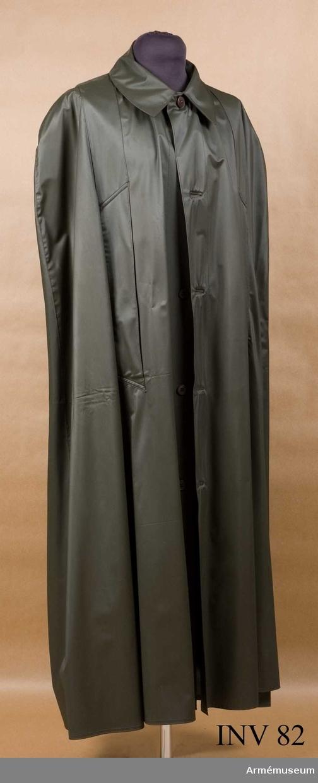 Av gråbrungrön plast. Nervikt krage. Knäppes med fem knappar. Två st ärmöppningar framtill. Har tillhört Gustav VI Adolf (1882-1973).