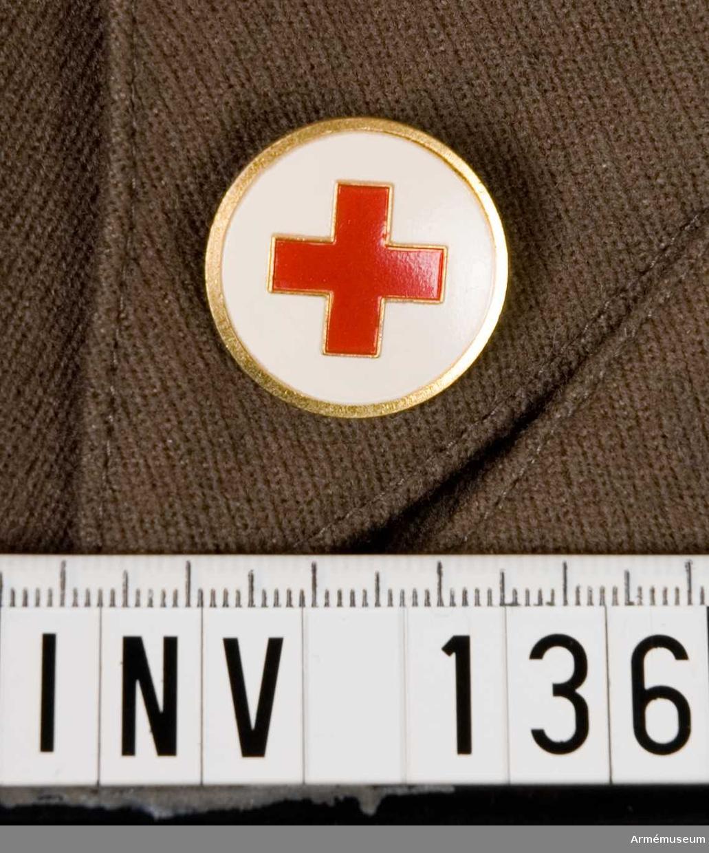 Samhörande nr är 132-144. Märke m/1939-1953?, SRK. Märkets framsida i mässing med vitmålad botten med ett rött kors. Baksidan har två runda hål avsedda för fastsättning.