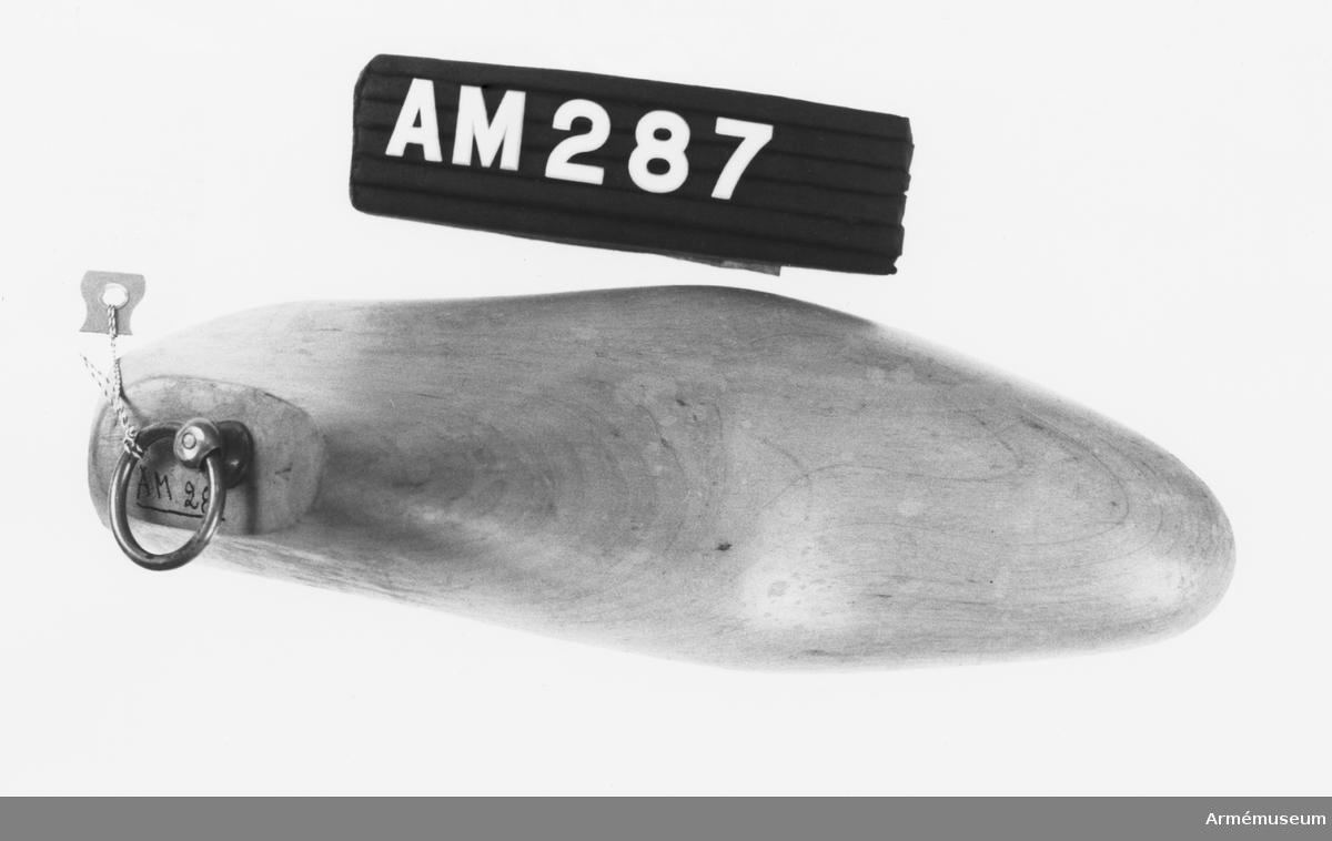 Blocket är format efter kängan i ett stycke trä. Försedd med dragring, diameter 30 mm, sittande i en ringhållare på skaft. Märkt V i sin övre del, synligt när blocket sitter i kängan.
