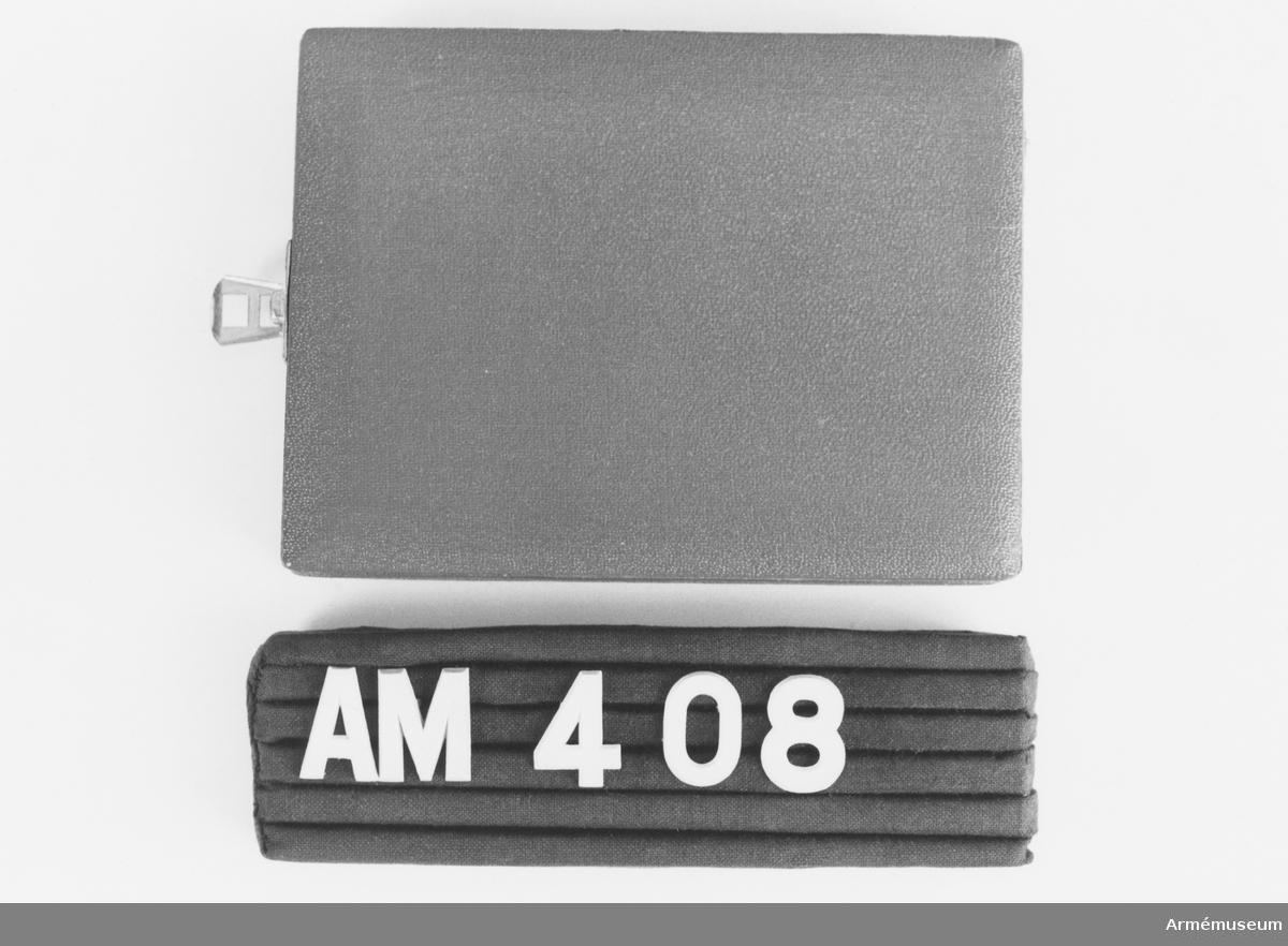 """Samhörande nr är 407-408 (294-299+321-350+400-448) Fodral t minnestecken för österikiska bergsdivisionen Innsbruck Mottaget under CA besök vid Österrikiska armén sep 1971. Pappfodral med lås i gulmetall. Invändig botten är klädd med svart sammet med fördjupning för skölden. Locket klätt med vitt konstsiden med märke för P K Pichlohg Innsbruck. """"Gångjärn"""" av vitt sidenband. Gott skick."""
