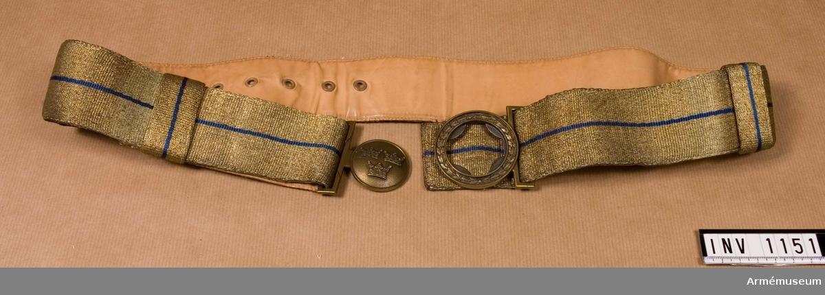 Av bronsfärgad metalltråd omgivande en smal blå silkerand. Bäres vid parad. Spänne av bronsfärgad metall. Den inre (då skärpet är knäppt) rundelen bär tre kronor, två över den tredje. Den yttre rundeln i spännet bär stiliserade blad. Skärpet är reglerbart, försett med sölja för att fasthålla den överskjutande tampen. Öljetterade hål på avigsidan och en hake för olika lägen. Skärpet är skinnskott med ljust läder.